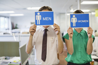 Business people holding 'men' and 'women' signs - CAIF02608