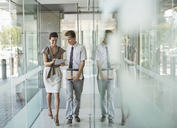 Business people talking in office hallway - CAIF02635