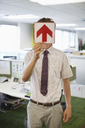 Businessman holding arrow sign in office - CAIF02650
