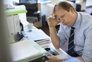 Businessman sighing at desk - CAIF02659