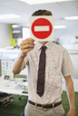 Businessman holding warning sign in office - CAIF02671