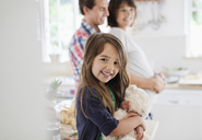 Girl holding teddy bear in kitchen - CAIF02677