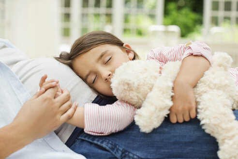 Girl napping on pregnant mother's lap - CAIF02686
