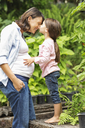 Girl kissing pregnant mother outdoors - CAIF02689