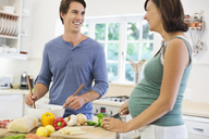 Couple cooking together in kitchen - CAIF02701
