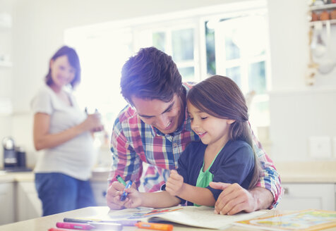 Father helping daughter use coloring book - CAIF02719