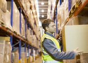 Worker stacking boxes in warehouse - CAIF02779