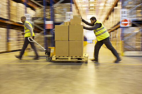 Workers carting boxes in warehouse - CAIF02782