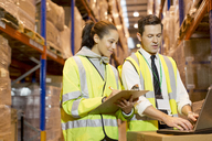 Workers using laptop in warehouse - CAIF02788