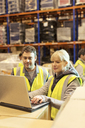 Workers using laptop in warehouse - CAIF02791