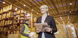 Businesswoman smiling in warehouse - CAIF02800