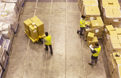 Workers carting boxes in warehouse - CAIF02803