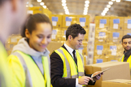 Businessman and workers in warehouse - CAIF02809