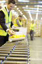 Businessman checking packages on conveyor belt in warehouse - CAIF02812
