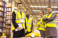 Businessman and workers smiling in warehouse - CAIF02815