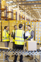 Businessman and workers talking in warehouse - CAIF02821