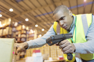Worker scanning boxes in warehouse - CAIF02830