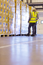 Workers examining stacks of boxes in warehouse - CAIF02836