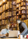 Workers using laptop in warehouse - CAIF02839