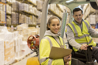 Workers smiling in warehouse - CAIF02842