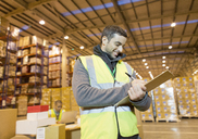 Worker writing on clipboard in warehouse - CAIF02845