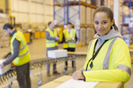 Worker smiling in warehouse - CAIF02851