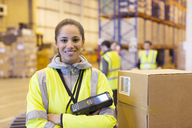 Worker holding scanner in warehouse - CAIF02860