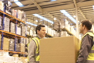 Workers carrying box in warehouse - CAIF02875