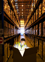 Worker opening glowing box in warehouse - CAIF02881