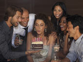 Woman blowing out birthday candles at party - CAIF02908