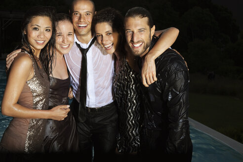 Friends in evening wear soaked by swimming pool - CAIF02929