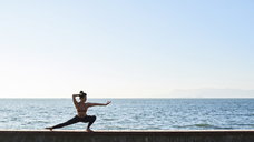 Young woman practicing yoga on a wall by the sea - IGGF00439