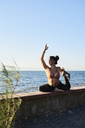 Young woman practicing yoga on a wall by the sea - IGGF00442