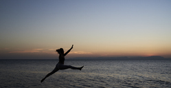 Young woman jumping at the sea at sunset - IGGF00448
