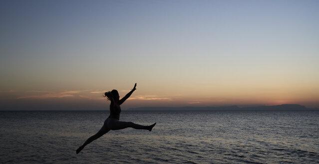 Young woman jumping at the sea at sunset - IGGF00448