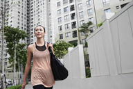 Confident fit woman walking in urban environment - IGGF00451