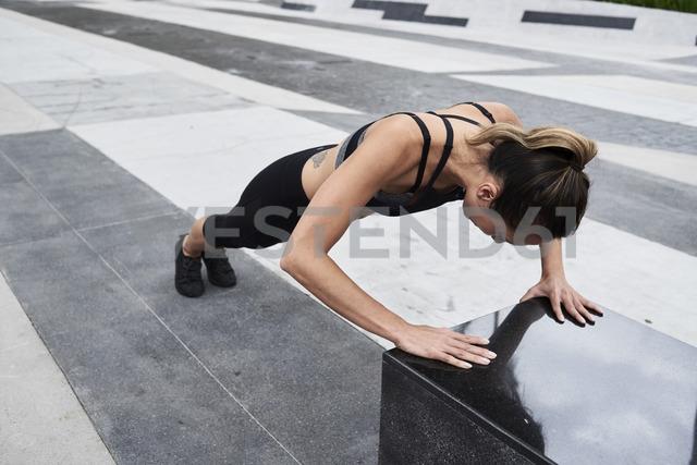 Fit woman doing push ups outdoors - IGGF00454