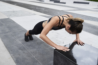 Fit woman doing push ups outdoors - IGGF00454