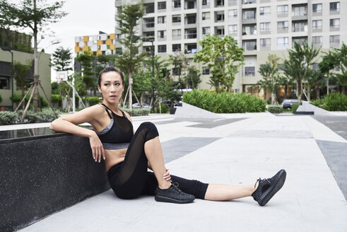Fit woman relaxing after exercising in urban environment - IGGF00457