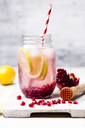 Fruit infused water with lemon slices, crushed pomegranate seeds and sparkling water - SBDF03472