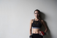 Portrait of confident female boxer against grey wall - IGGF00464