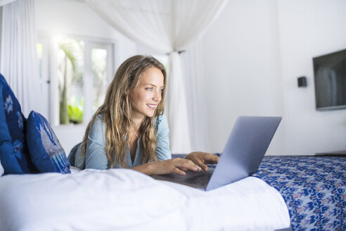 Smiling woman lying in bed using laptop - SBOF01418