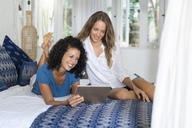 Two smiling women in bed using tablet - SBOF01424