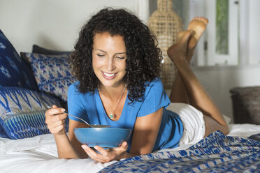 Smiling woman lying in bed eating a bowl of muesli - SBOF01427