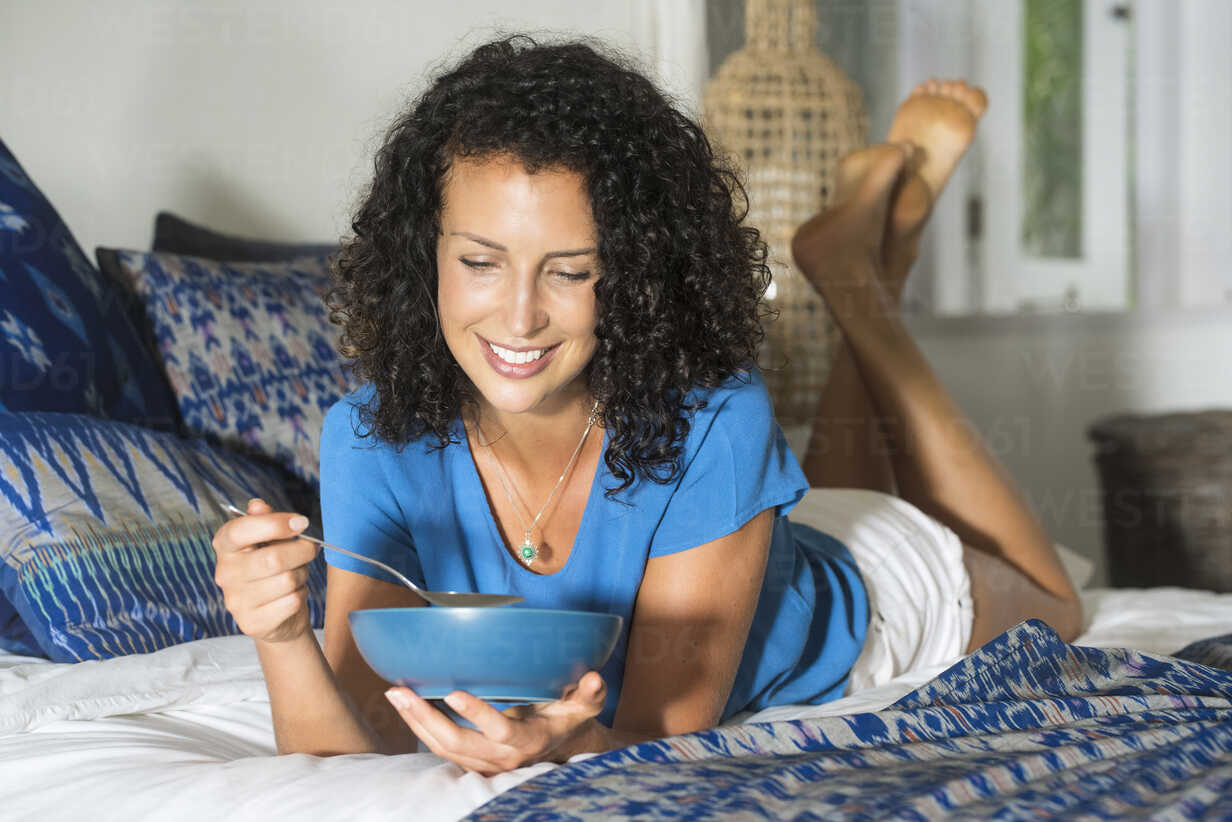 Smiling woman lying in bed eating a bowl of muesli - SBOF01427 - Steve Brookland/Westend61