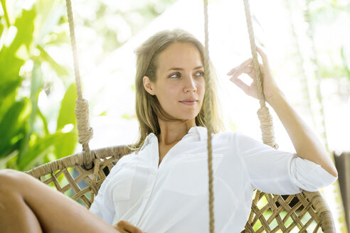 Smiling woman relaxing in hanging chair - SBOF01436