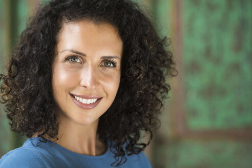 Portrait of smiling woman with curly hair - SBOF01442