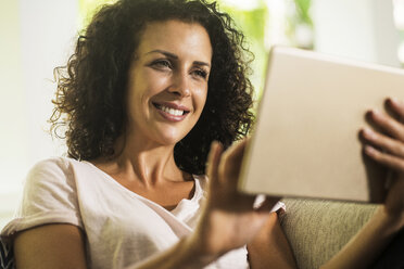 Portrait of smiling woman using tablet - SBOF01445