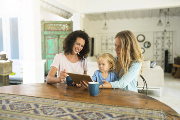Two women with a child looking at tablet at kitchen table - SBOF01454