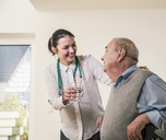 Senior man smiling at nurse holding glass of water at home - UUF12870
